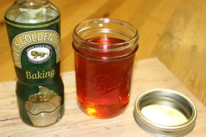 Lyle's Golden Syrup bottle next to homemade golden syrup in wide mouth Mason jar