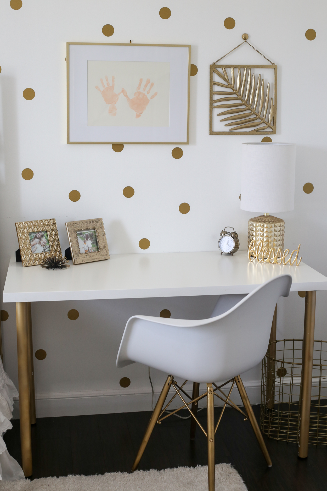 The desk station with golden accents and a white chair.