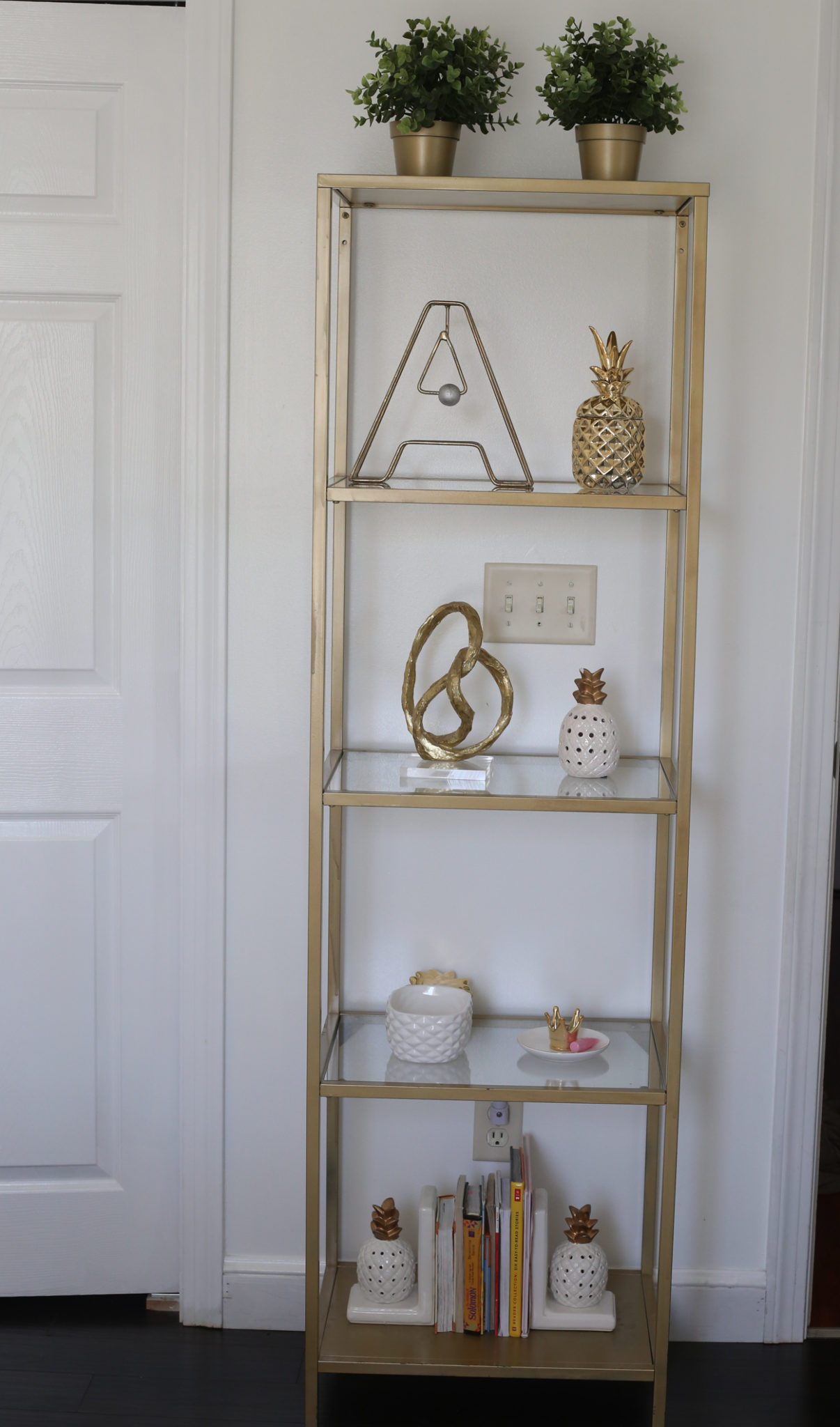 Golden book shelf loaded with golden decor accents.
