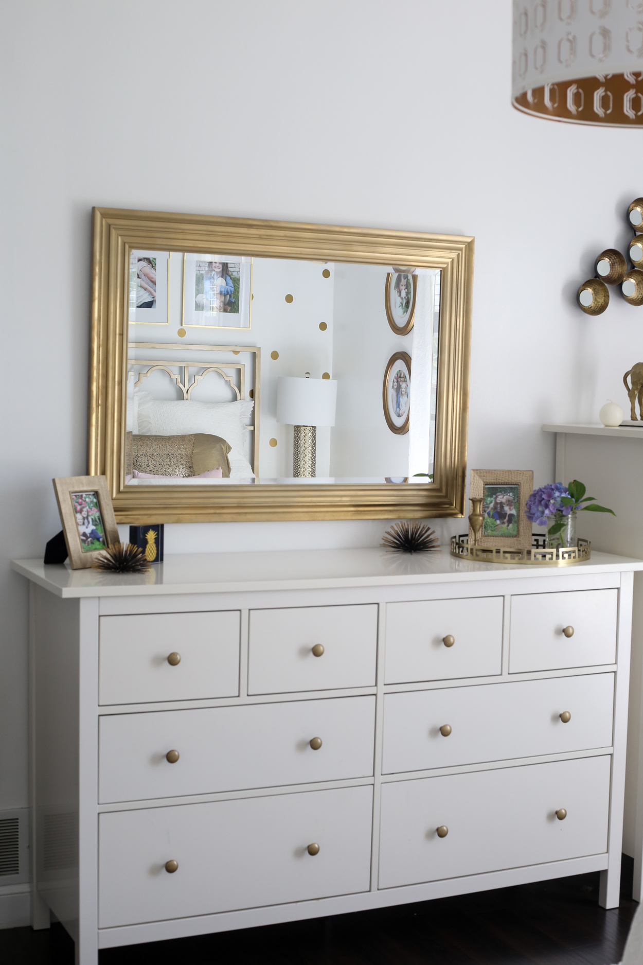 A white dresser topped with gold accents with a gold mirror above it.