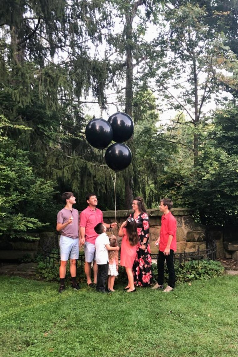 Family standing by three black balloons ready for gender reveal.