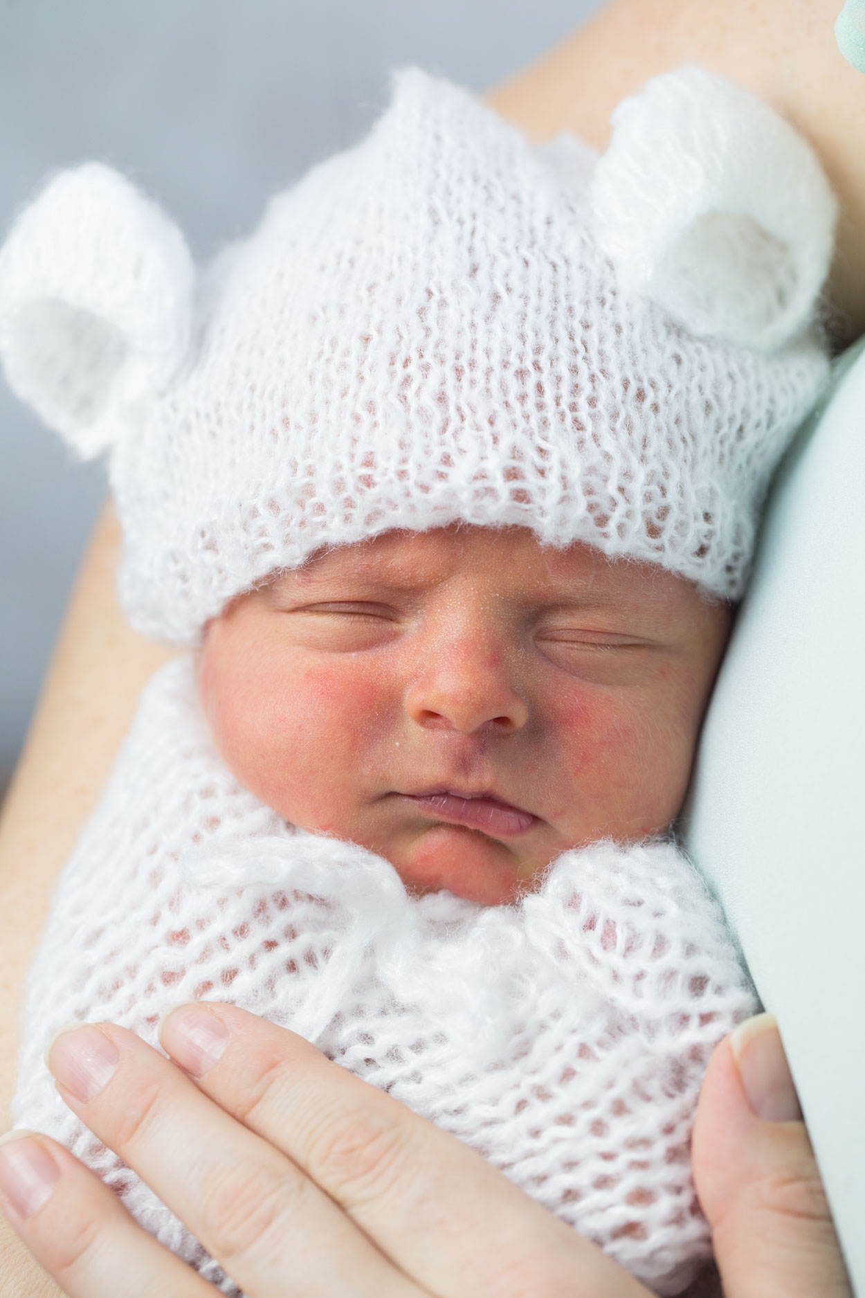 Baby swaddled wearing a hat and sack.