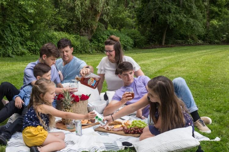 A family having a picnic outside on a blanket.