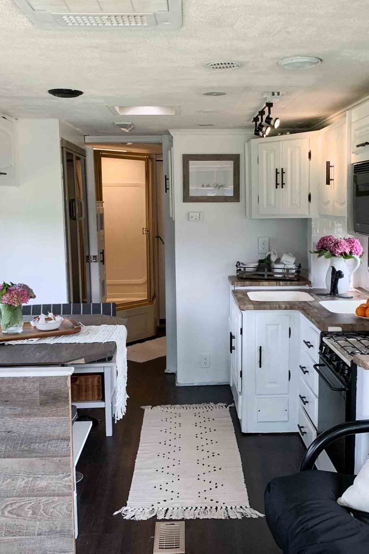 A picture of the inside of an RV shiwing the kicthen and dining area.