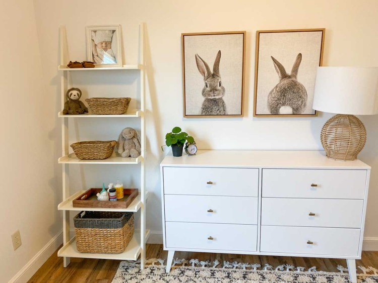 A dresser next to a wall shelf with decor on the shelves and bunny art over the dresser.