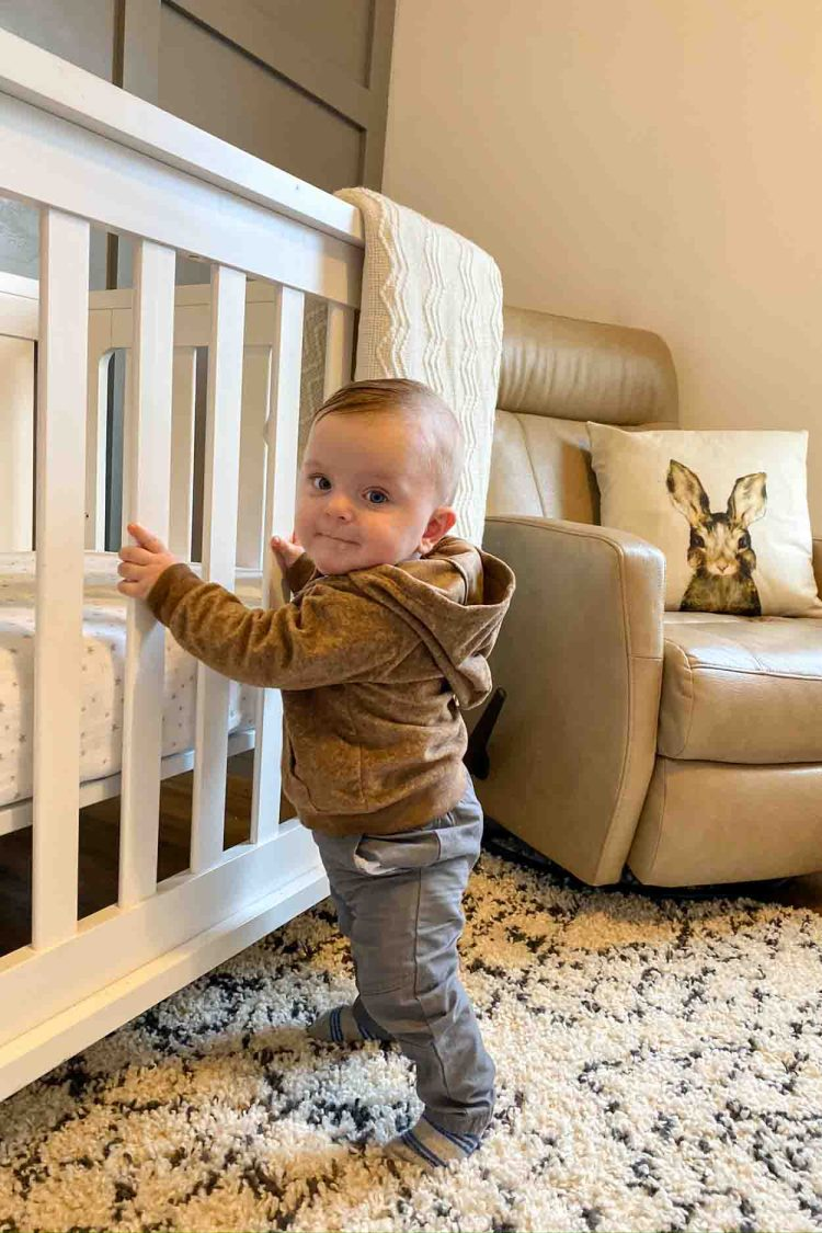 Baby standing next to white crib next to a rocking chair.
