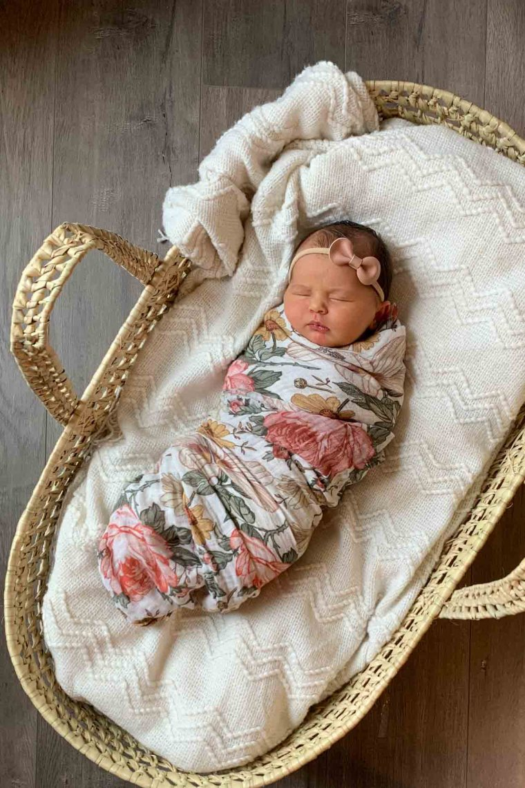Baby in a basket with a white blanket and wrapped in a floral blanket.