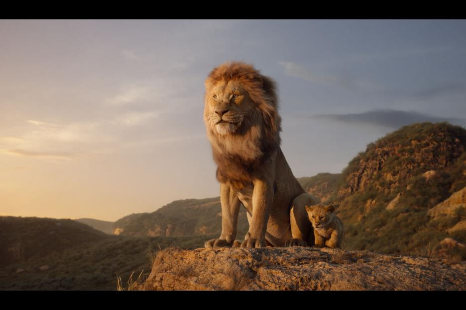 Young Simba and Mufasa sit upon Pride rock. Lion King Movie