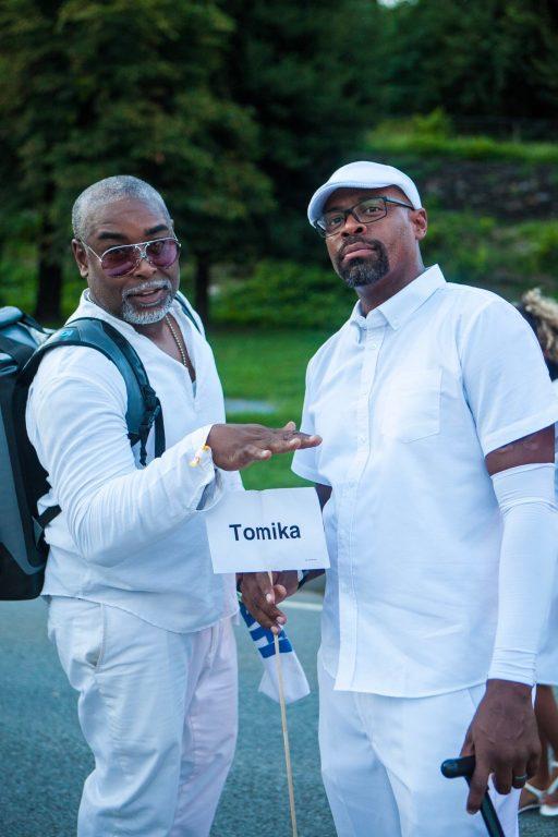 Brown men holding sign at Diner En Blanc