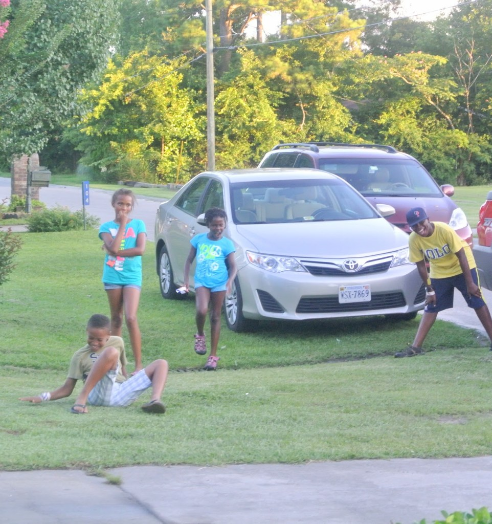 Brown Skin Kids playing outside near a late model Toyota