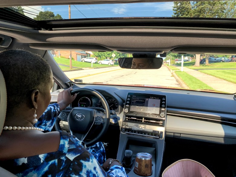 Brown girl doing safety checks before road trip in hybrid Toyota Avalon 2020