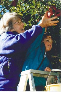 Lois Petre picking apples with grandson