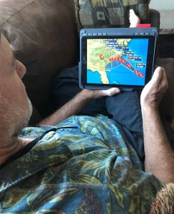 Dean watching hurricane on iPad