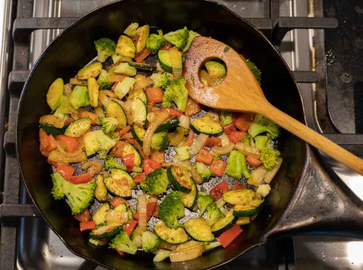 zucchini, onions and peppers frying in a cast iron skillet