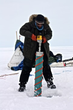 Craig Aumack drills an ice core.