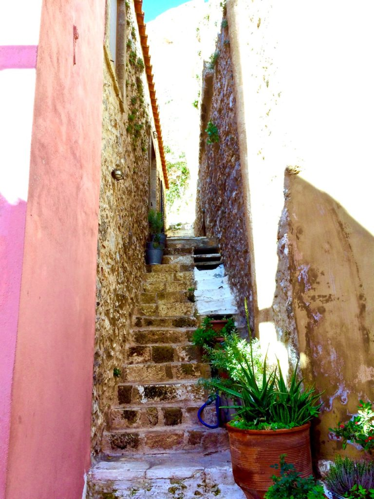 Monemvasia's old town cobble stoned passageways and steps lined with green pot plants