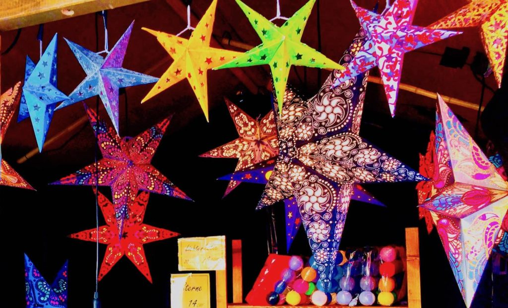multi-coloured hanging plastic stars in Christmas market stall