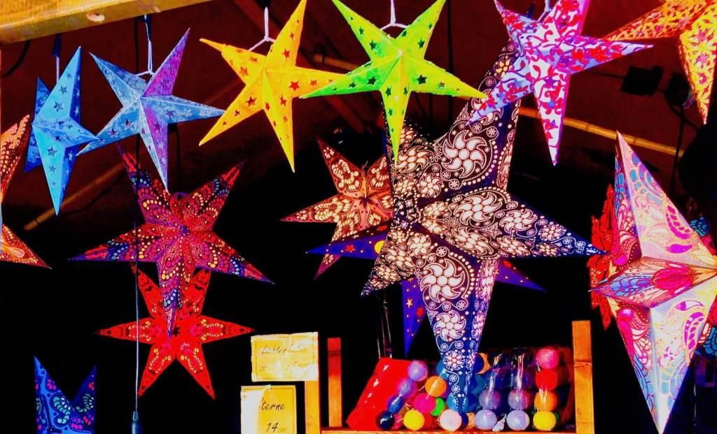 multi-coloured hanging plastic stars in Christmas market stall