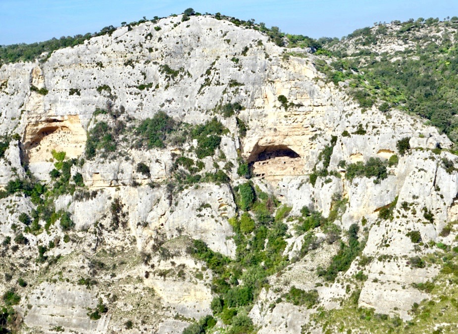 Holes in a canyon wall mark the graves of prehistoric people