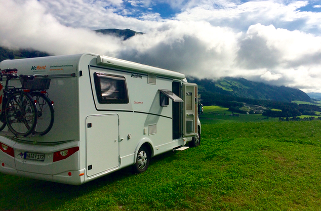 campervan high in the mountains of Austria on the green grass looking down into the valley
