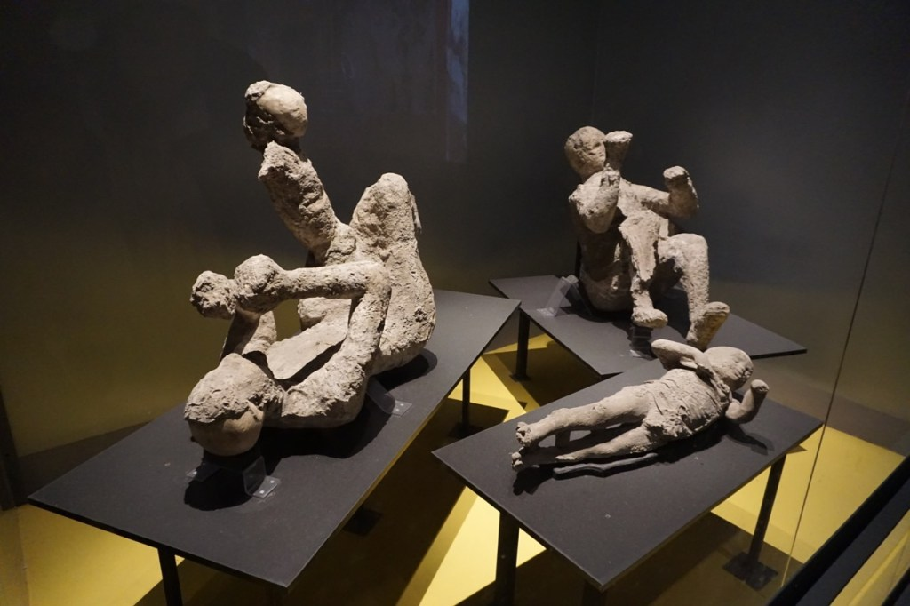 Mummified casts of a father with his son on his knee and two other young people