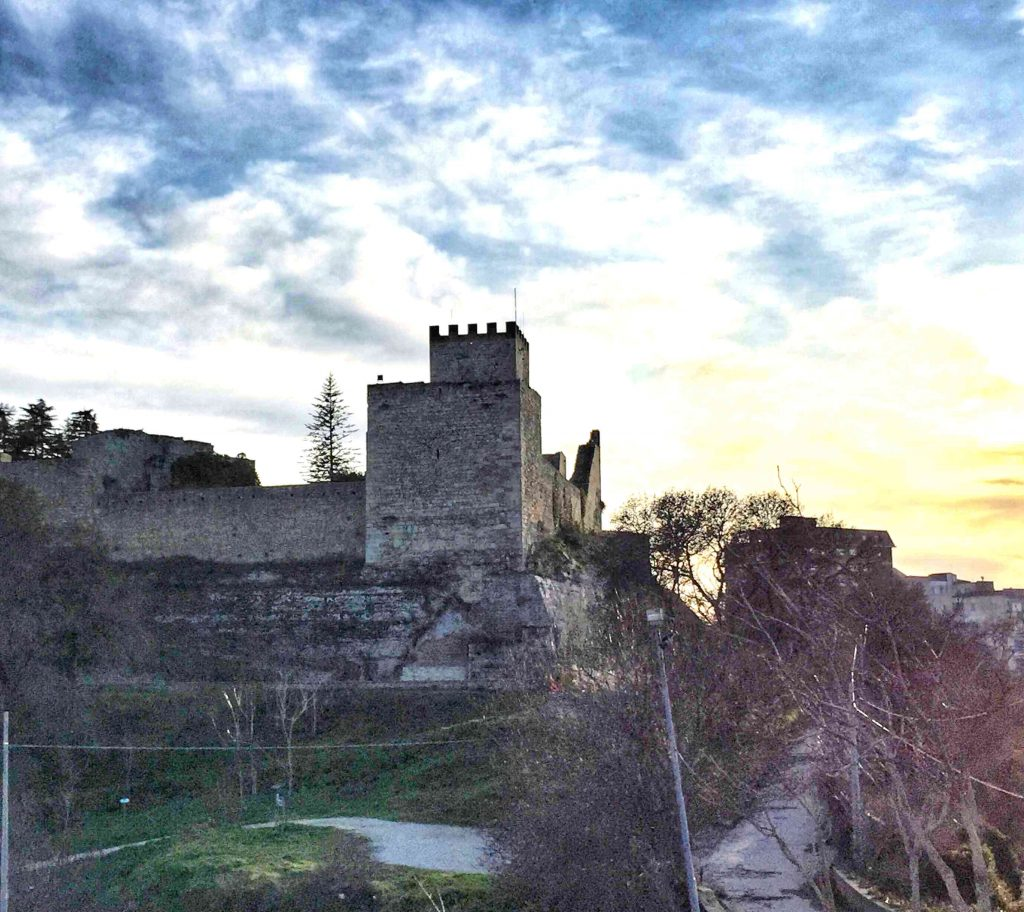 Grey castle on a hill with a darkening blue late afternoon sky