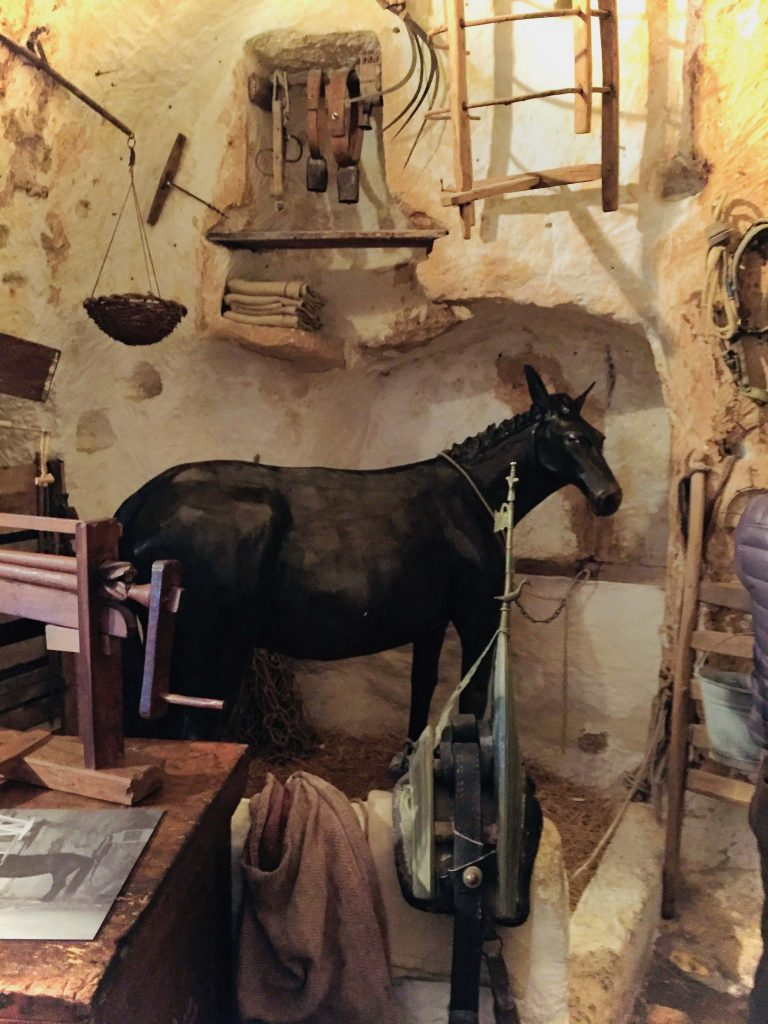 different types of tools hanging on the wall, including a wooden ladder. A model horse is stood on hay in an area just big enough for it to fit. There is a small hanging basket, a straw broom to the side.