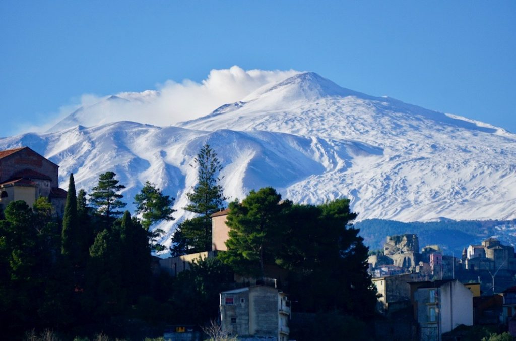 White snowy peaks of Mt Etna with green trees in the foreground