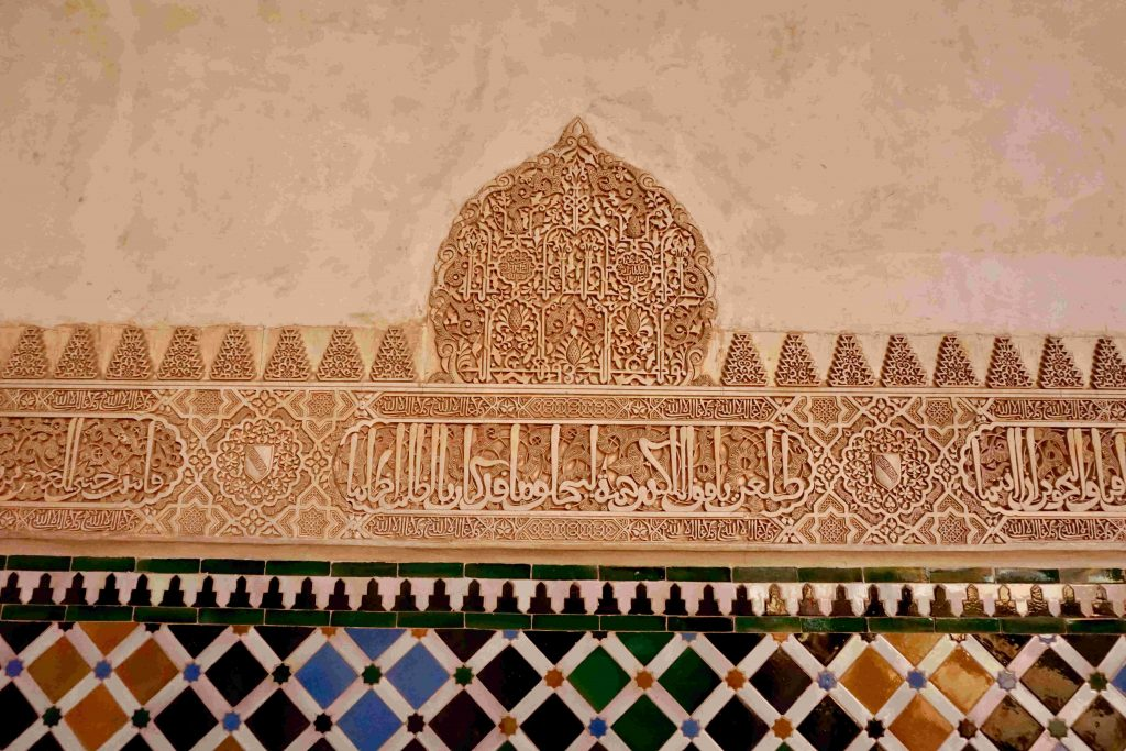 some tan coloured intricate arabic writing embedded in a cornice.
