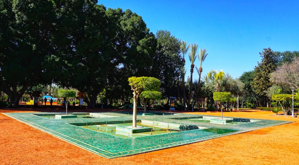 Green tiled fountain with green trees in the background