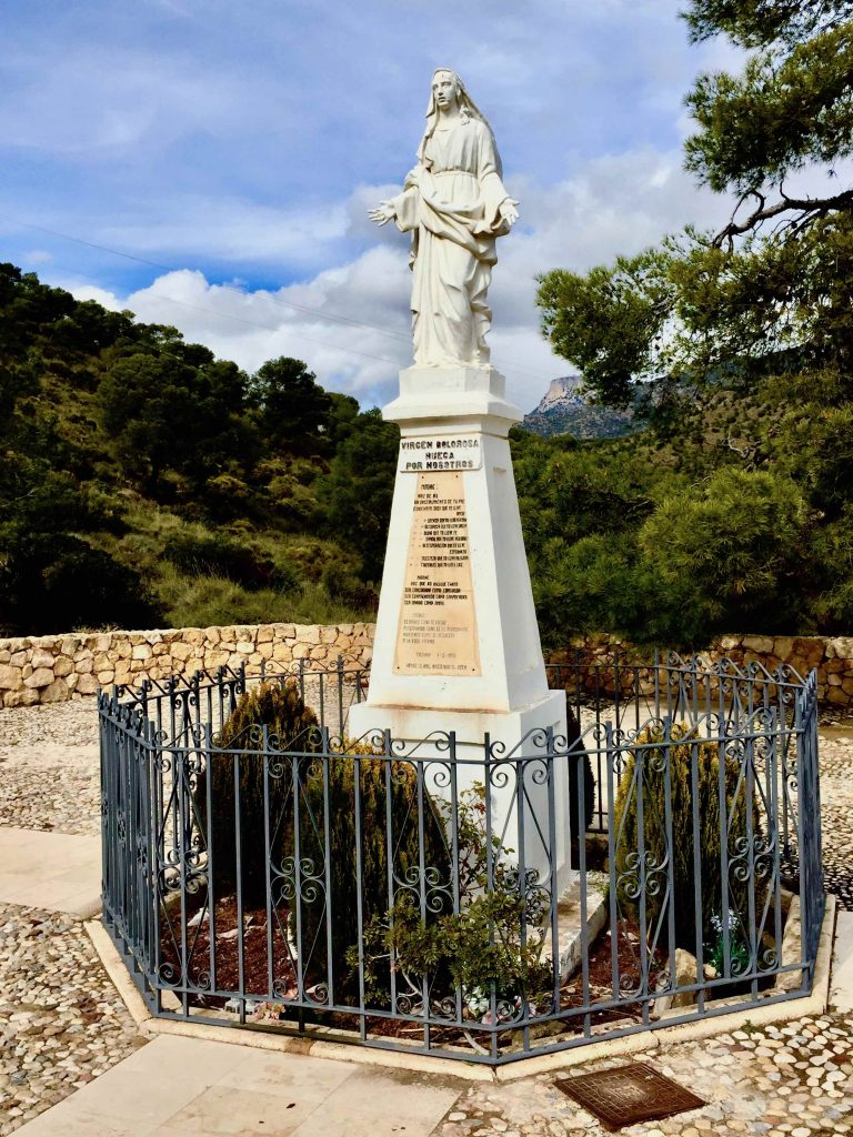 A tall white statue of the Madonna with a small fence around it