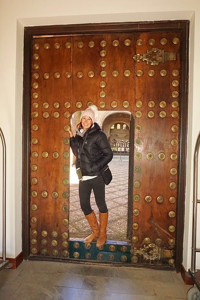 Michelle standing against an old wooden door with brass patterned discs on the door