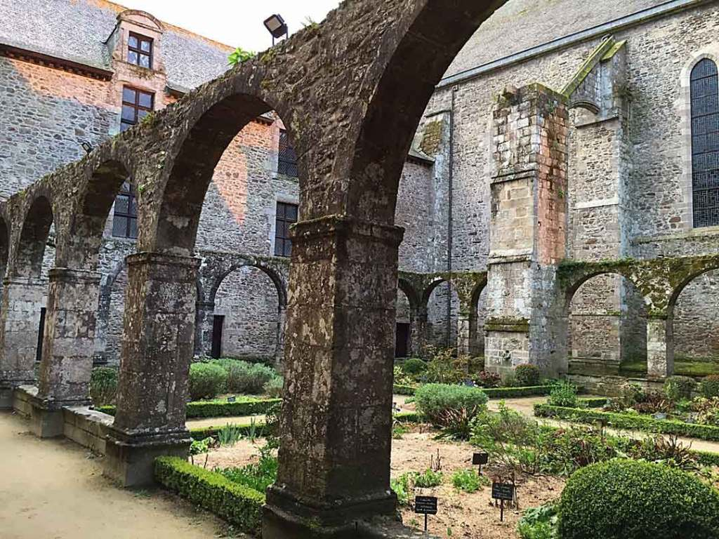Dilapidated church with archways surrounding a garden