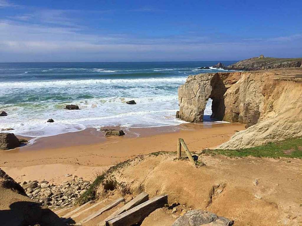 Rock arch in a foamy blue sea