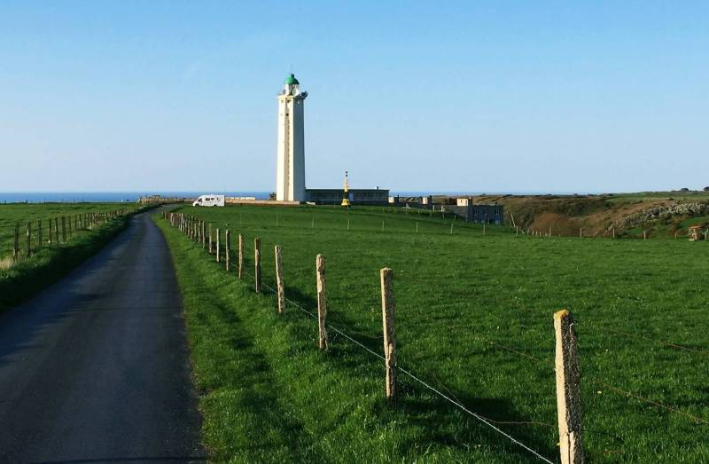 The lighthouse is in th background, tall white with a green top and in the foreground is a green field and single track road .There is a white campervan parked by the lighthouse.