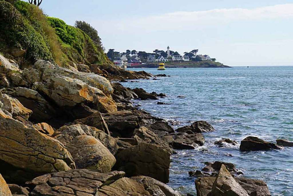 Rocky sea front in front of a peninsula of houses