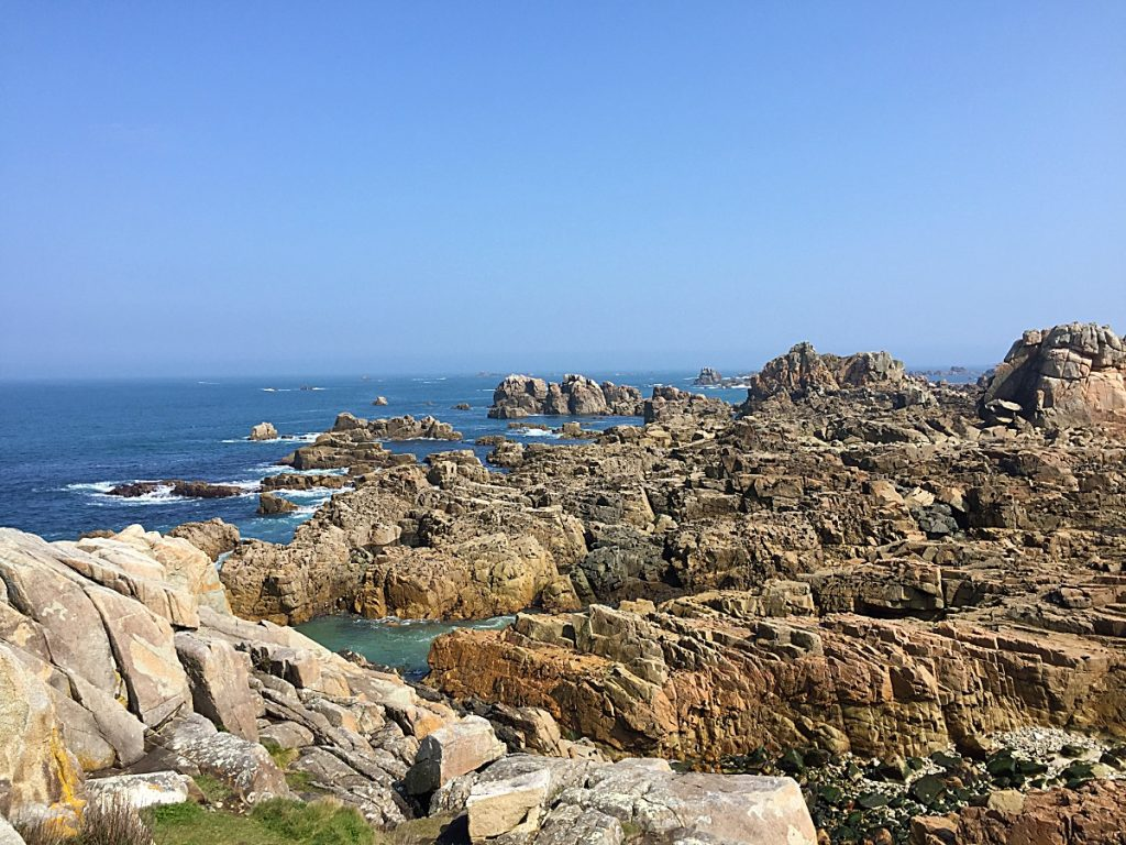 Rocky coastline with a blue sky and green tinged sea