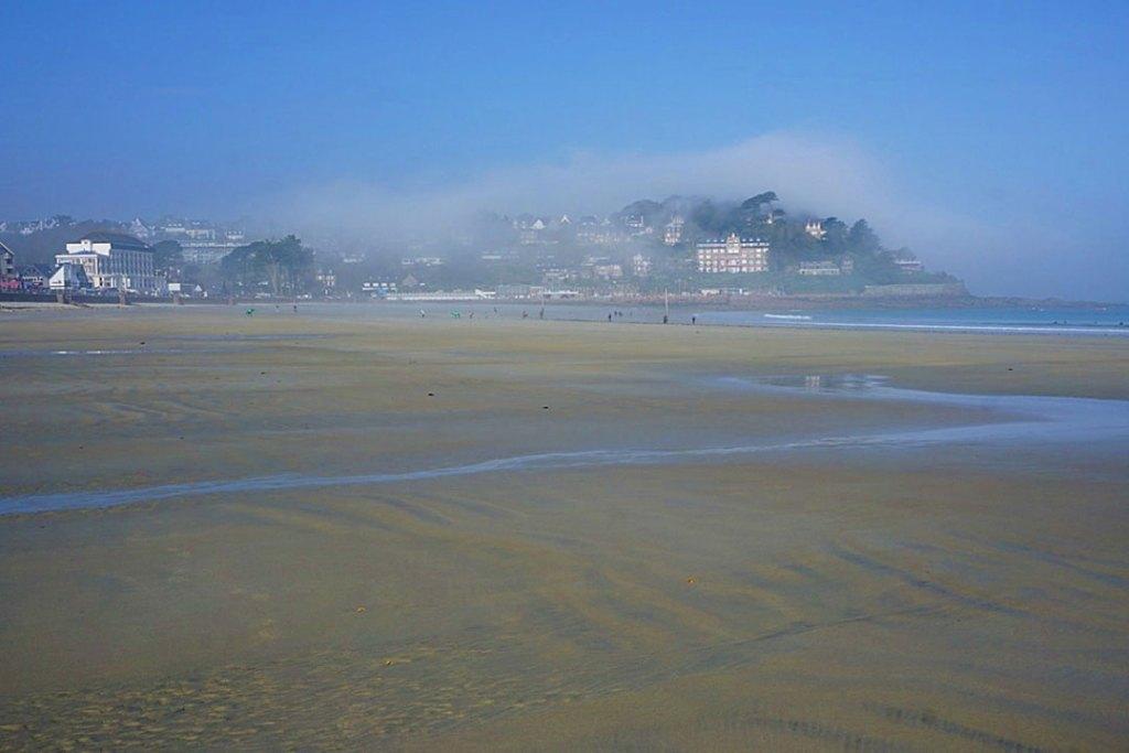 Fog shrouding a hill top seen from a wide beach