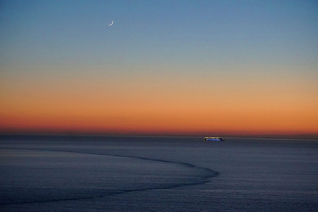 twilight with a boat in the distance and the crescent moon
