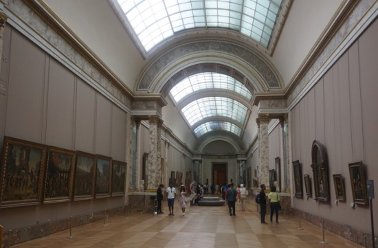 Inside the hall of Louvre Museum wiht paintings on either side