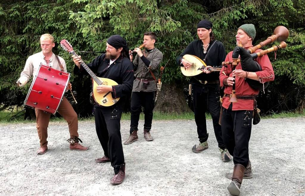 Five musicians dressed in viking clothes one with a flute, one with drum, two with guitar like instruments and a bag pipe looking instrument.