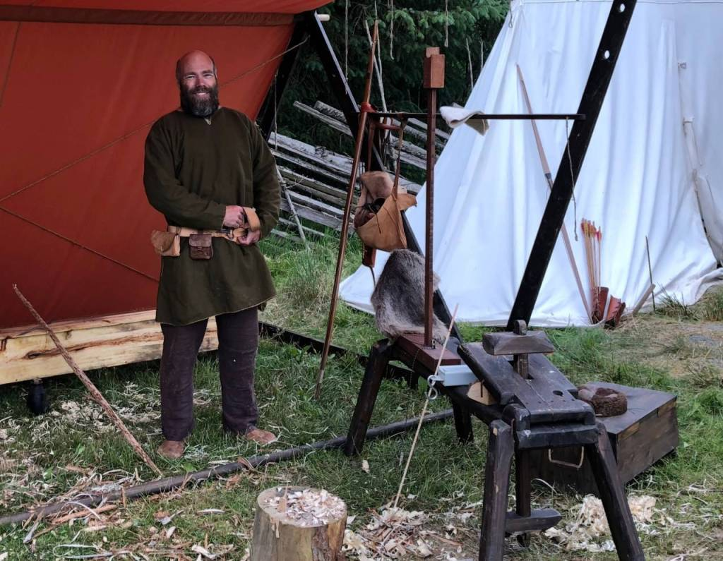 A man dressed as a viking with a dark green cloak and dark trousers. In front of him are wood shavings and an old wooden vice beside him