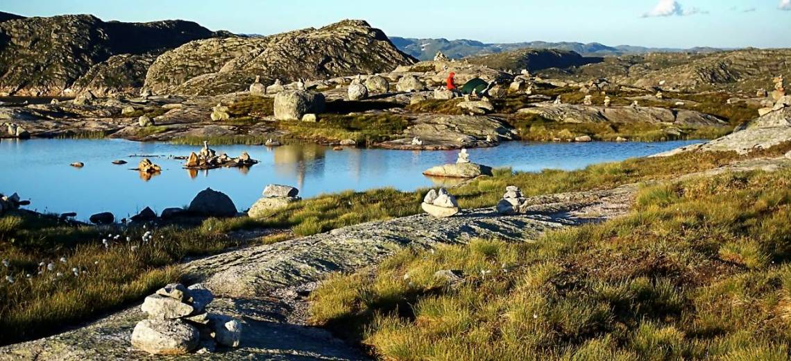 a small still lake with craggy rocks surrounding it. I the background amongst the rocks is a small dark green, tent and a person in a bright orange top.