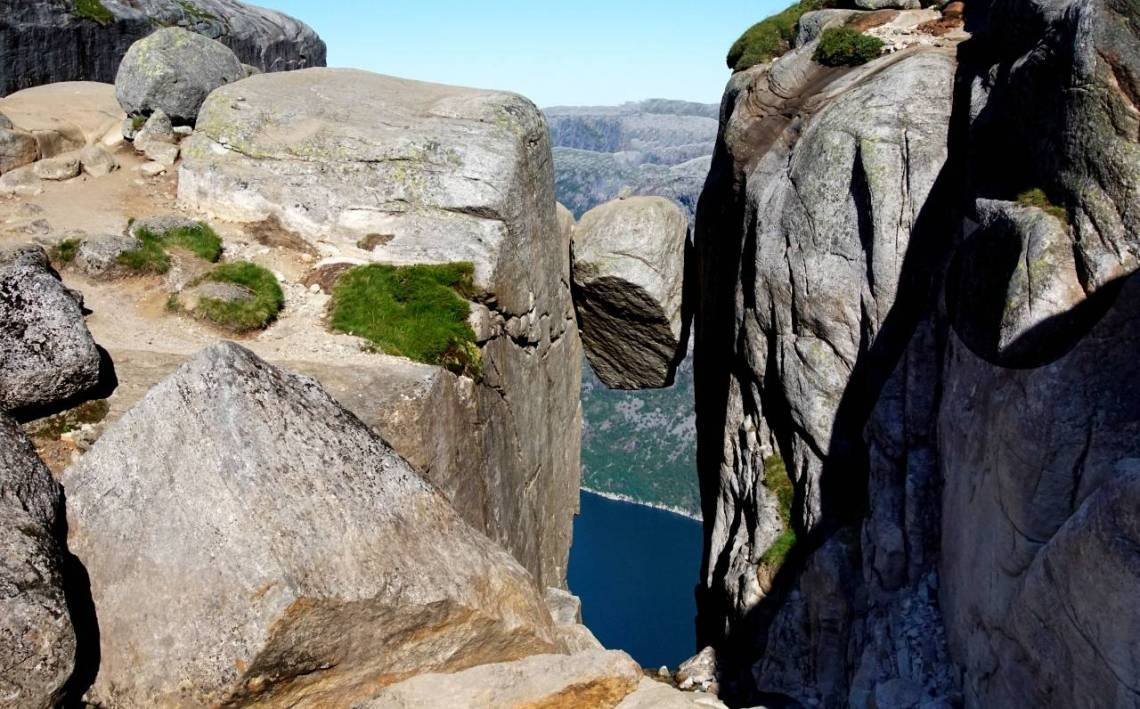 Kjeragbolten - A rock the size of a large car wedged between two rock faces with a fjord at the bottom of the photo