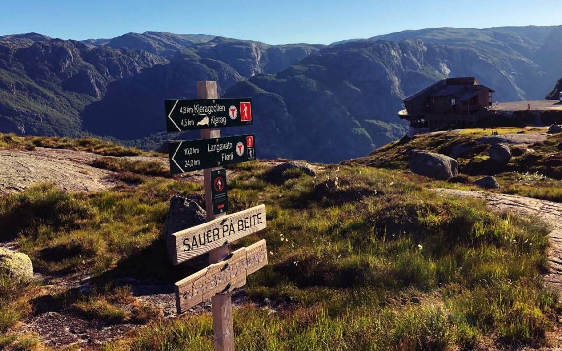 a wooden sign showing the direction to kjeragbolten is 3.5km. Mountains in the background.