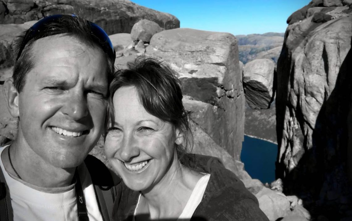 Lars and Michelle in black and white with the only colour showing is the blue of the sky and the blue of the fjord way down below. In the background is the Kjeragbolten boulder wedged between the two rock-faces