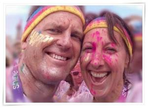 A picture of a man and woman showing their faces smiling. Both have coloured powder paint on faces and multi-coloured headband.