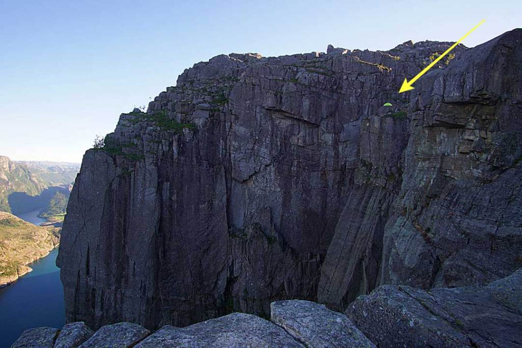 Views from the Preikestolen plateau showing a pitched tent on a nearby cliff face