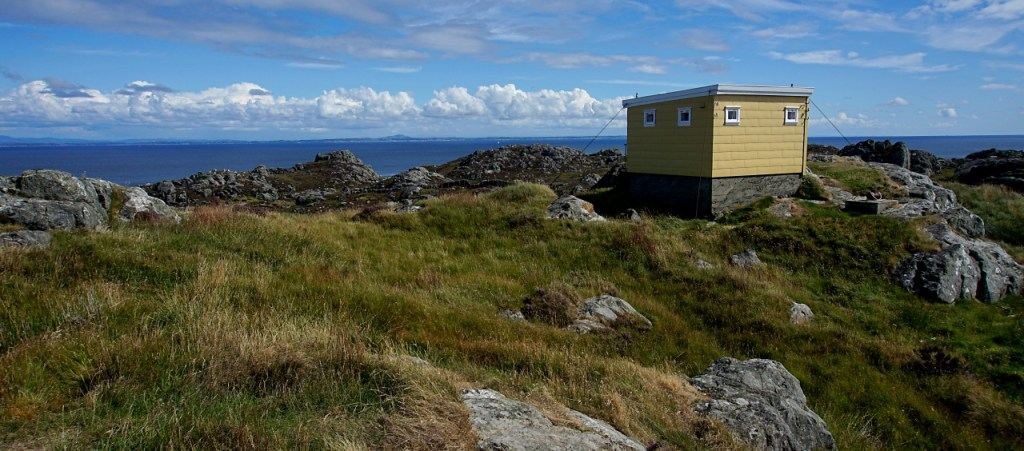 The yellow square hut on the to of the hill - the sea can be seen in the background.