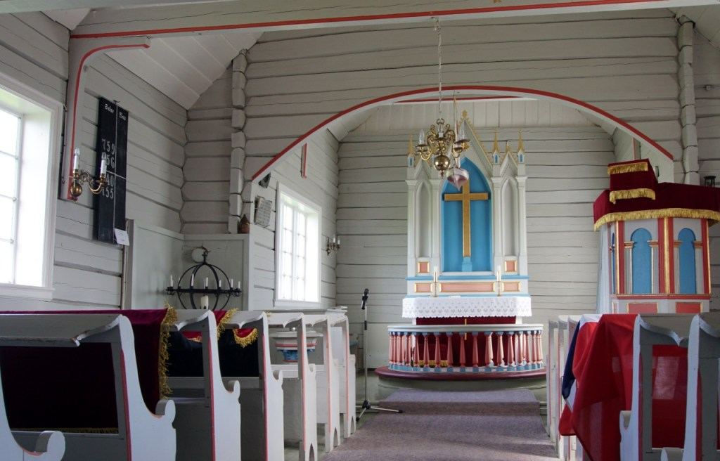 Inside the church the walls are white with pink trimming and the alter has a gold cross surrounded by a pale bright blue.